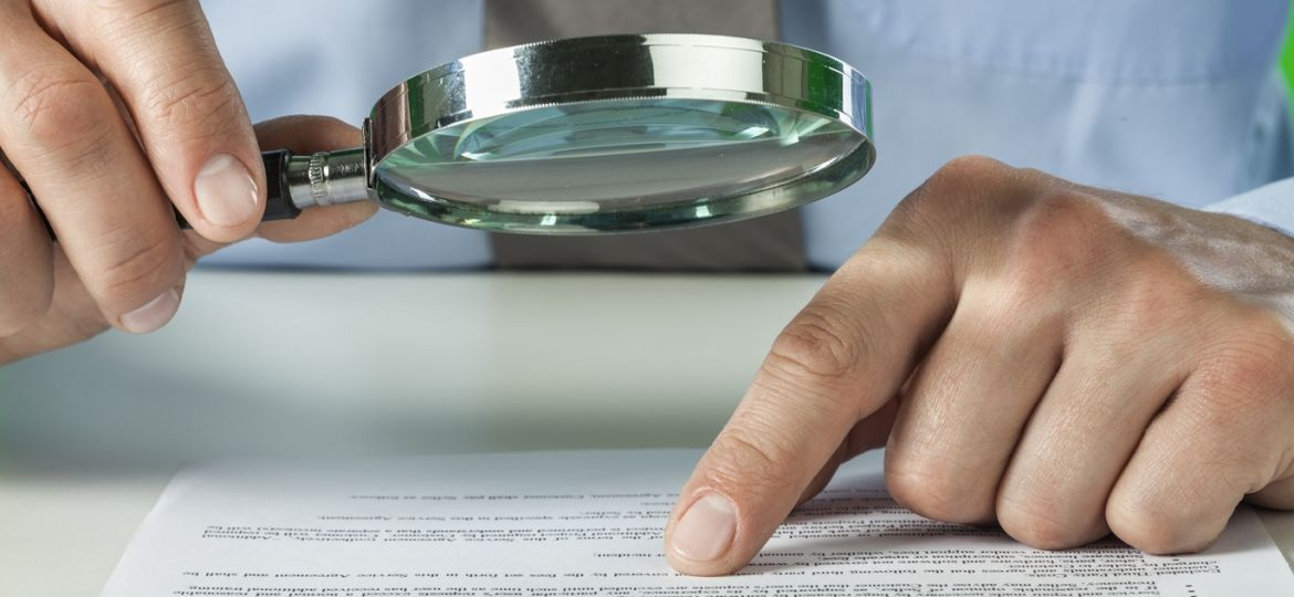 Businessman reviewing document with a magnifying glass