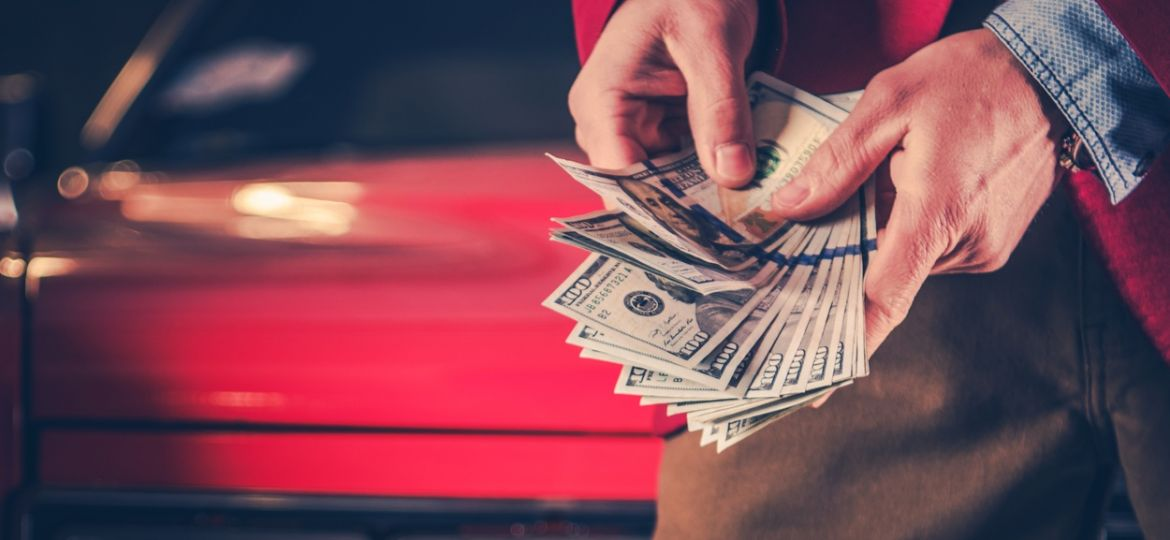 Man holding cash in front of a red car
