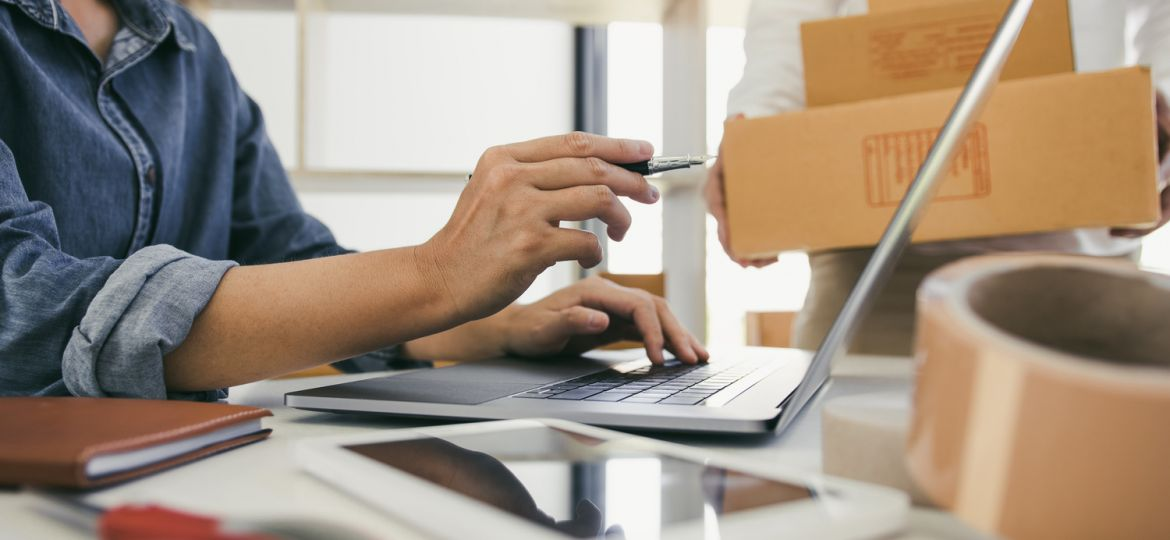 Businesswomen working on laptop with Male co-worker holding three boxes