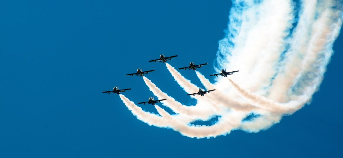 Fighter flies in the smoke in the blue sky aerobatics