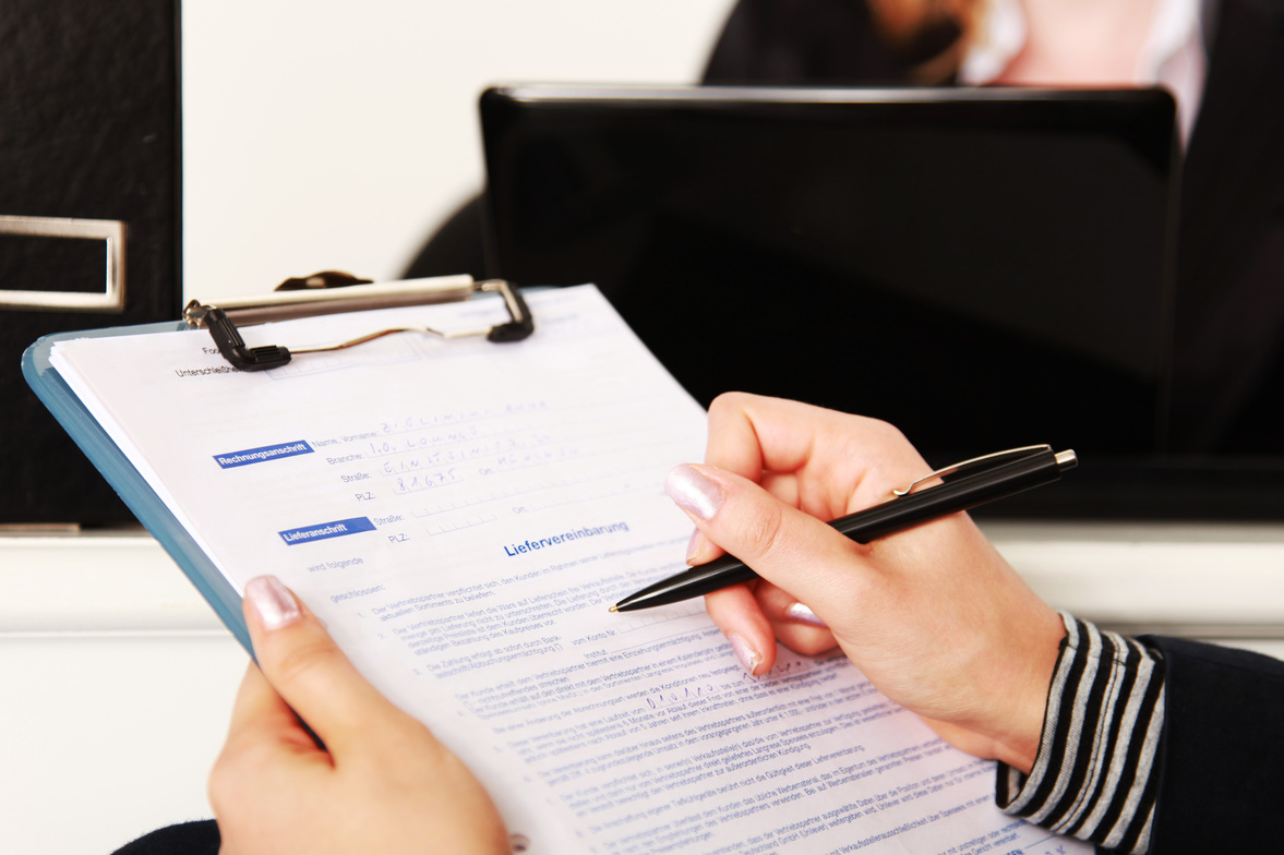 Womens hand checking a document with black pen