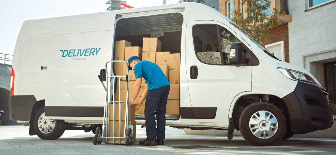 Courier Takes out Cardboard Box Package From Opened Delivery Van Side Door. Professional Courier / Loader helping you Move, Delivering Your Purchased Items Efficiently