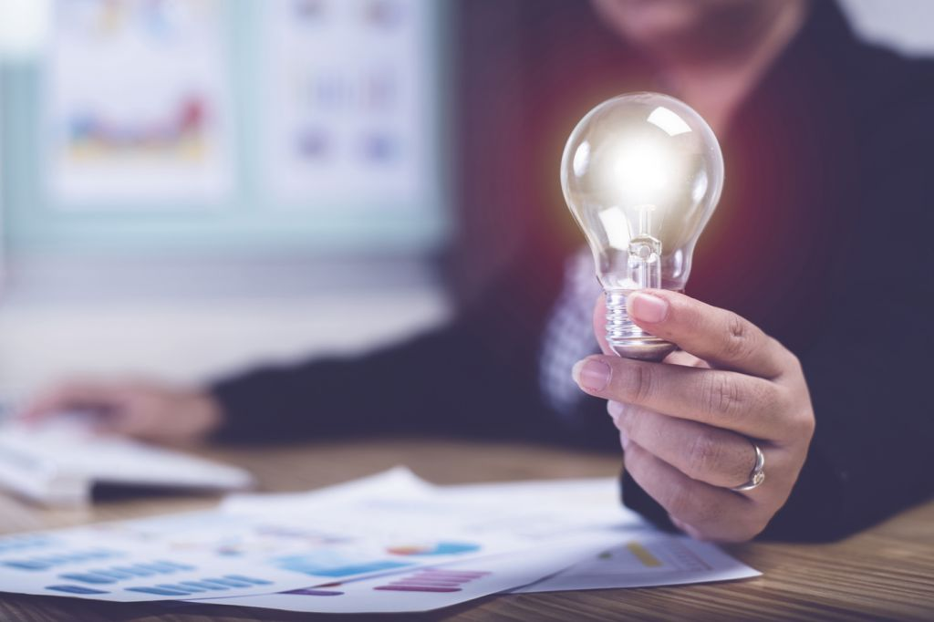 Asian businesswoman hand hold light bulbs at home office desk background | Concept idea and innovation.