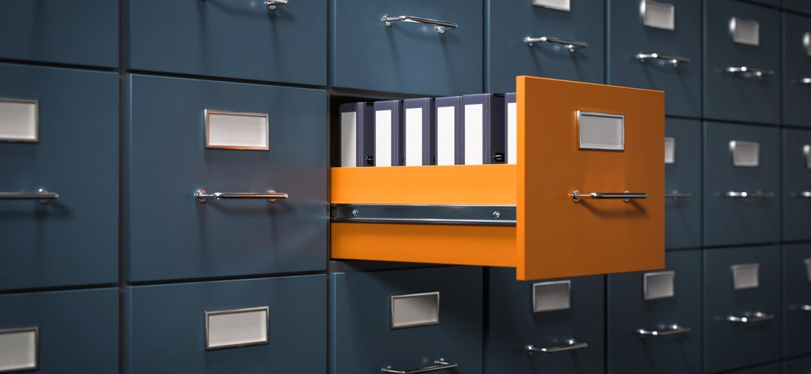 Open Yellow Filling Cabinet Drawer with Blue Binders among Closed Blue Cabinet Drawers