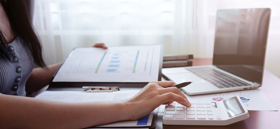 Businesswoman working on calculator with laptop at home or office.