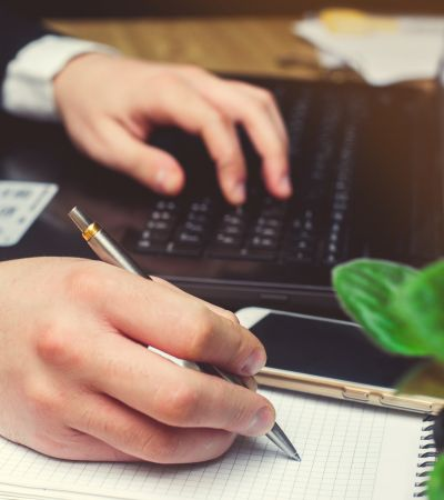 Hand of businessman in suit on keyboard filling and signing with a silver pen documents. Finance and accounting business background. wood table and using contemporary notebook